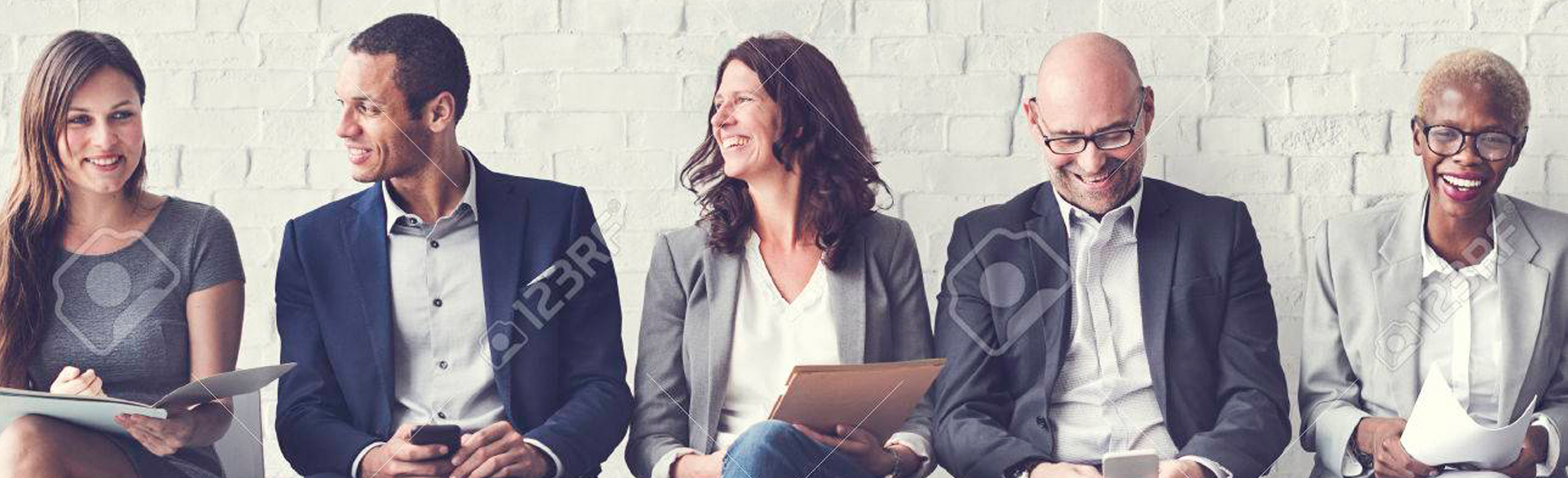 5 people sit in a line holding their resumes
